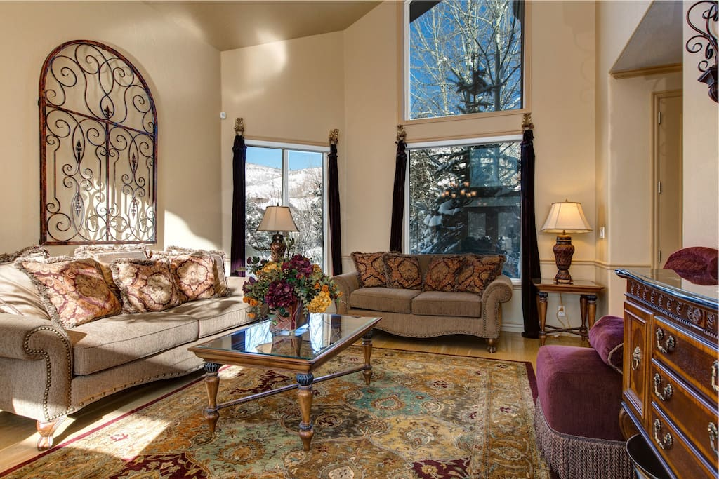 The sitting room is furnished with 2 love seats, 2 plush purple chairs, and ornate pillows and rugs