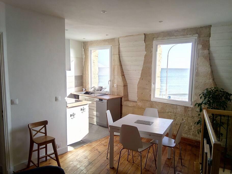 Coin repas et cuisine avec deux grandes fenêtres sur la mer