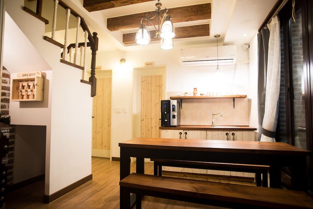 현관문을 열고 들어서면 보이는 뷰 샹데리아,싱크대,정수기,테이블