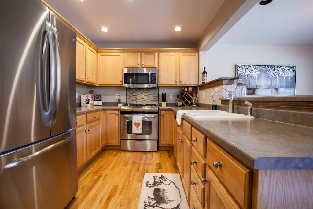 Fully equipped kitchen, open to dining and living room.