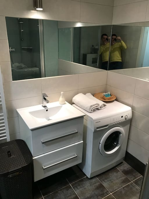 Bathroom with washing machine, shower, toilet, foen, towels, shampoo