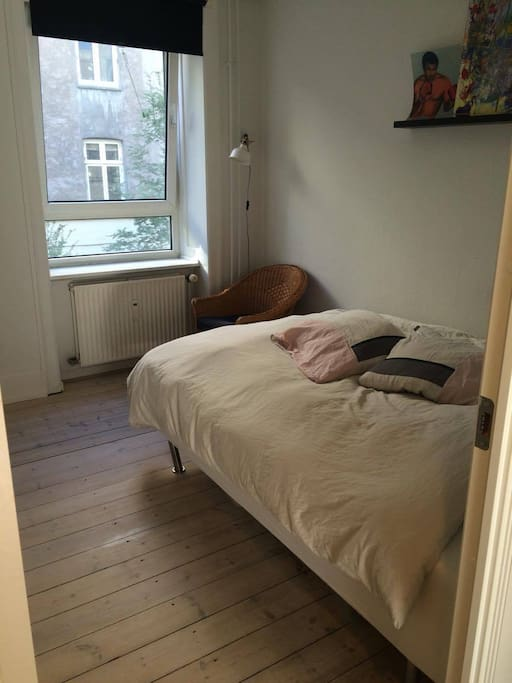 bedroom with a double bed and a big window with blackout curtain. The bedroom is out to a quiet courtyard so you wont hear the noise from the streets