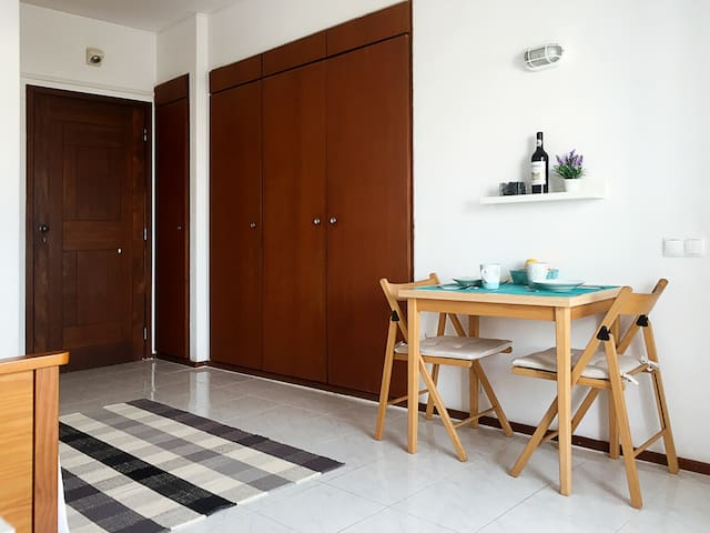 Entrance door, large wardrobe, beds and table.