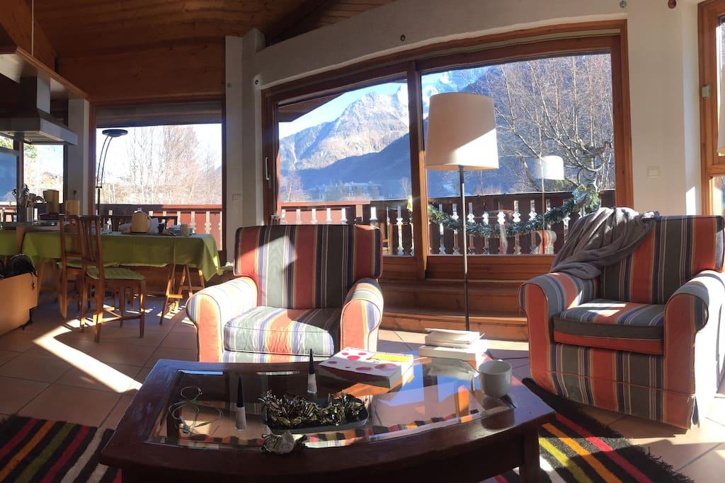 Vue vers terrasse avec coin repas et montagne