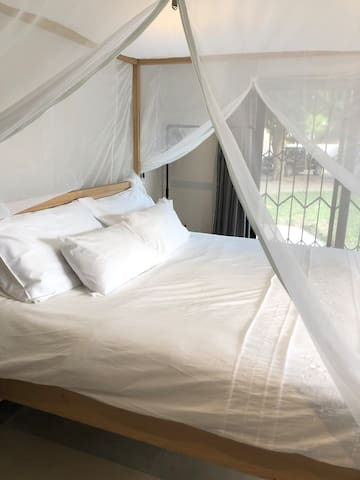 Main bedroom with king size bed and perfect fit mosquito net for ultimate peace sleep