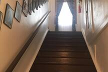 This is the private stairway leading up to the second floor 4 room suite/apartment  available for overnight stays.  The second floor was once a 10 room frontier hotel. The pictures on the wall are the previous owners from 1840-today.