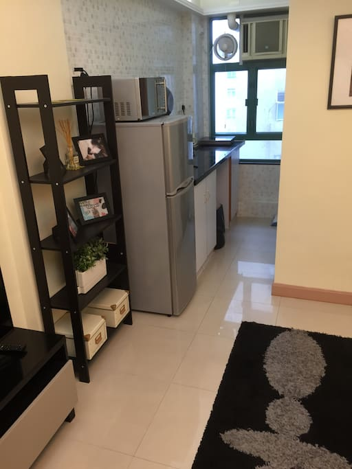 Kitchen with refrigerator, cooking hob and microwave