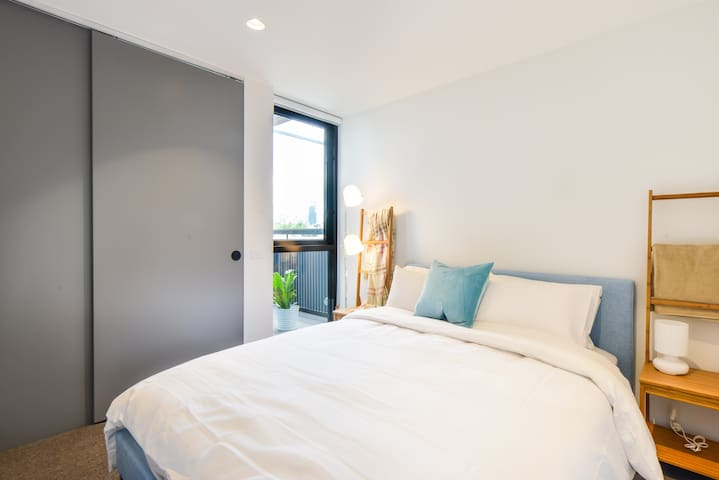 The bedroom is replete with a plush headboard, comfortable queen bed, large closet and window that lets in natural light