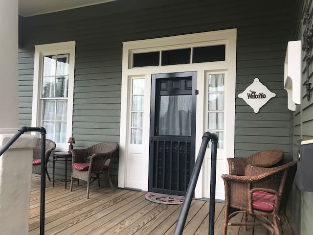Covered front porch includes 4 wicker chairs, table and lamp