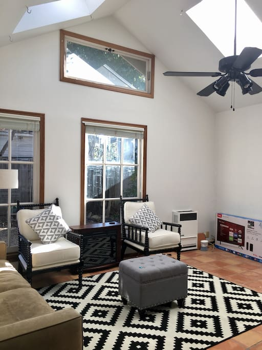 Soaring ceilings w/ 4 skylights make the space airy & infused with natural light. A brand new TV is at the corner now.