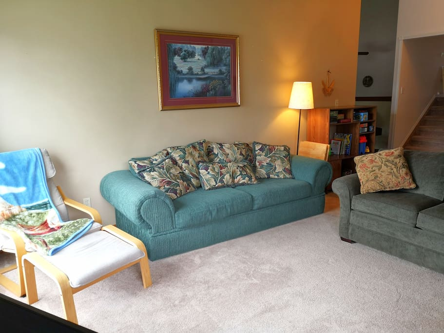 LIVING ROOM - 2 full sized couches, chair & ottoman, and entertainment cabinet, with a view to the dining room and short stairway to the bedrooms & bathroom on the upper level