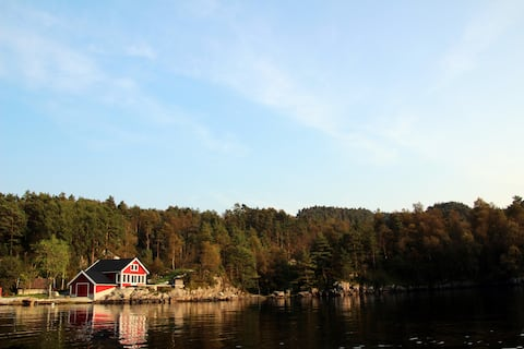 Hytte med boblebad og båt ved fjordkanten
