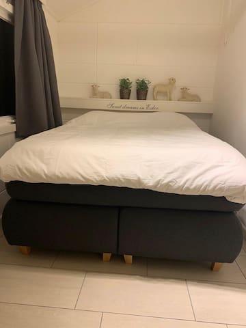 Slaapkamer 1: Goede luxe nieuwe 2 persoons boxspring met topper zodat er geen spleet tussen de matrassen zit. In de kamer zit een ruime inbouw kast. U treft bij aankomst uw bed opgemaakt aan en voorzien van handdoeken en gastendoekjes.