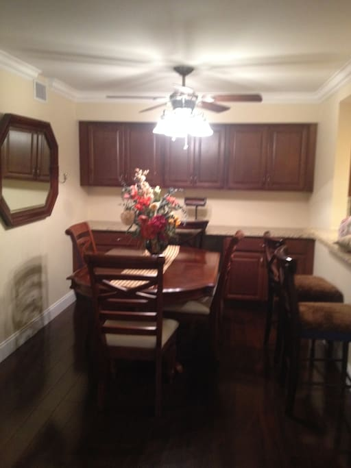 Dining room table with 6 chairs and office space along wall