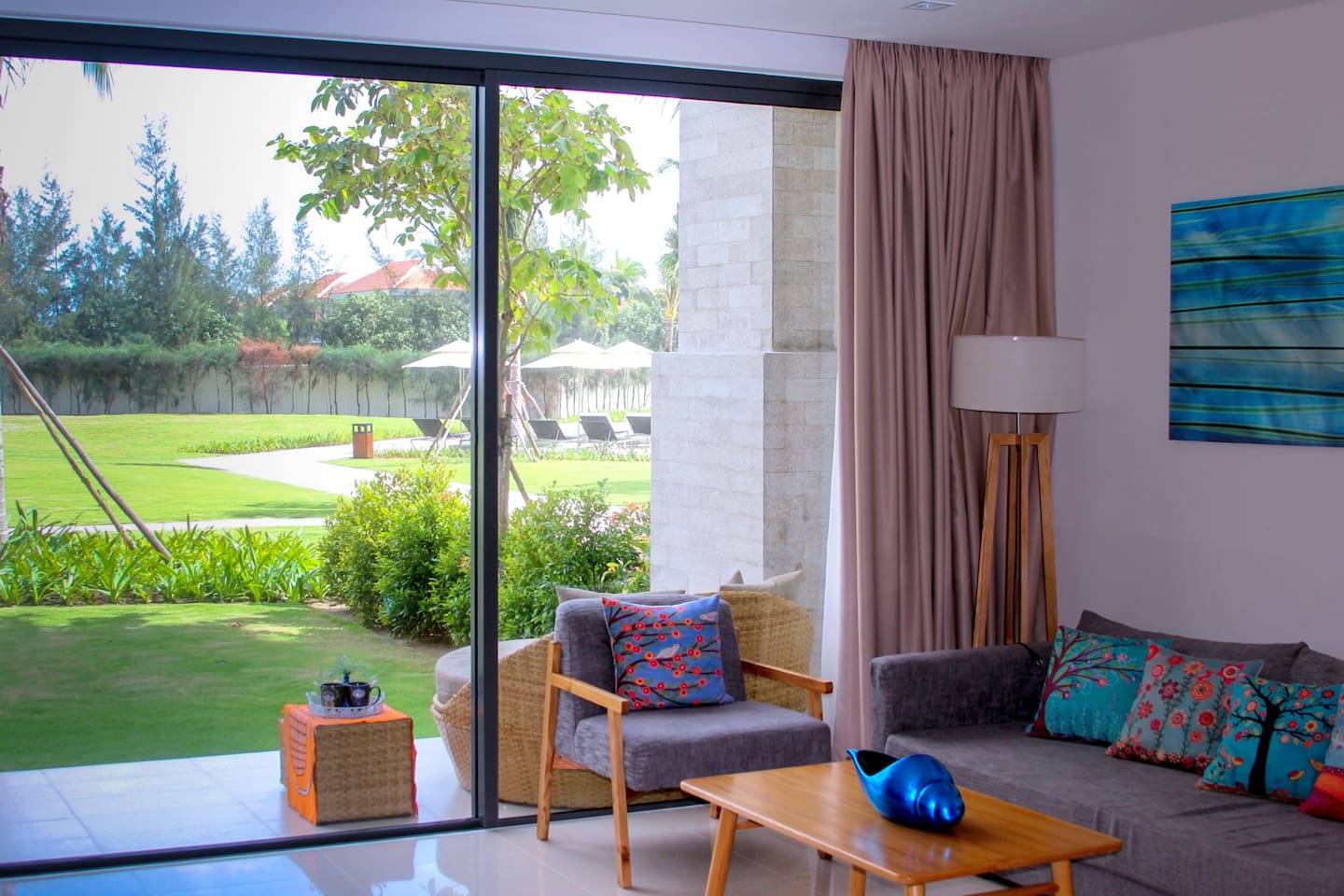 The living room is connected with the beautiful greenery outside. The pool is to the right of the garden.