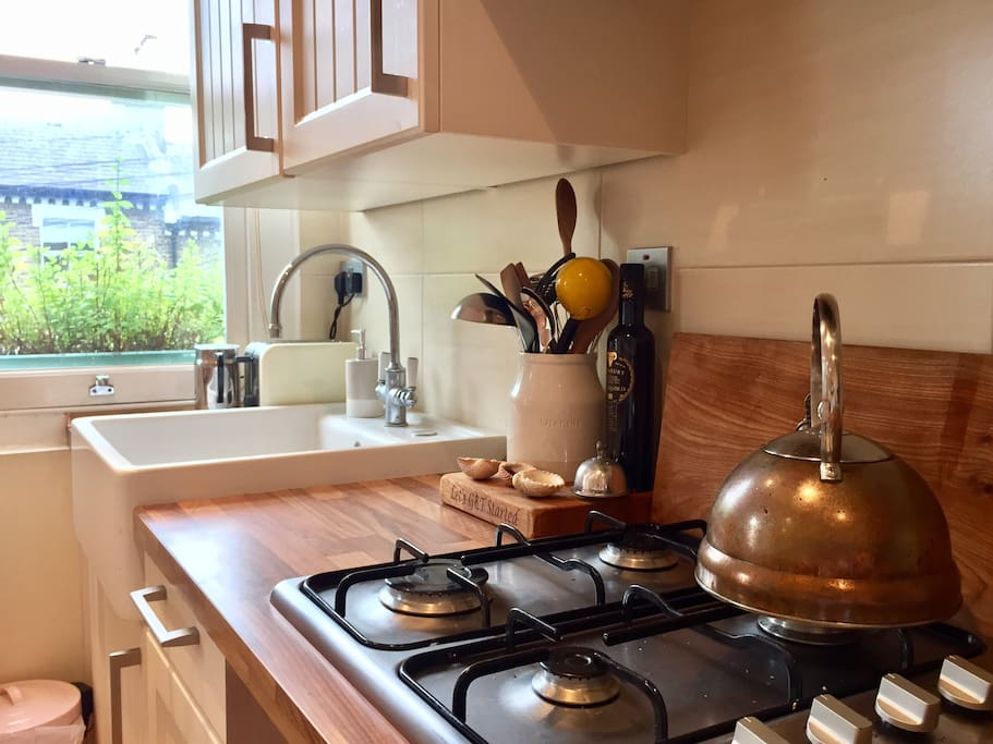 Fully equipped stylish kitchen with standalone copper kettle.
