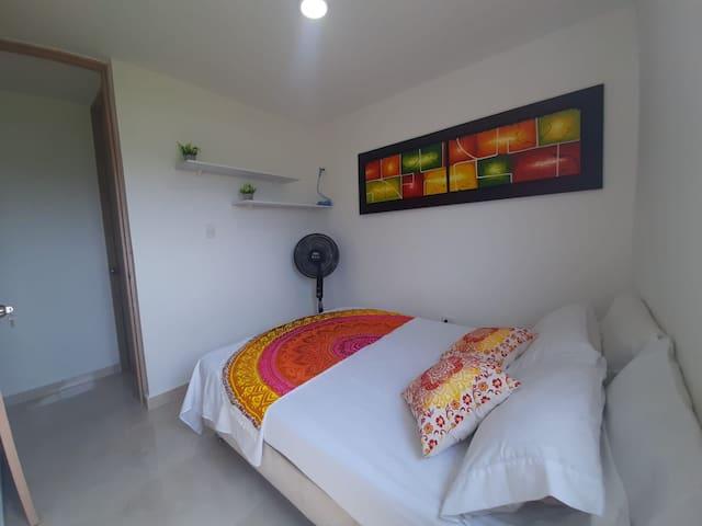 Habitación con cama doble, buena iluminación y ventilador portátil