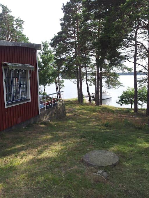 Stugan till vänster med den lilla altanen. Nedanför ser ni vattnet och den egna bryggan.