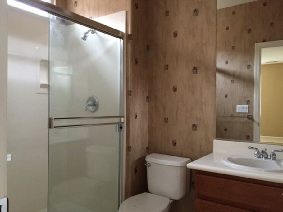 Full size bathroom with soap, shampoo and bath towels.