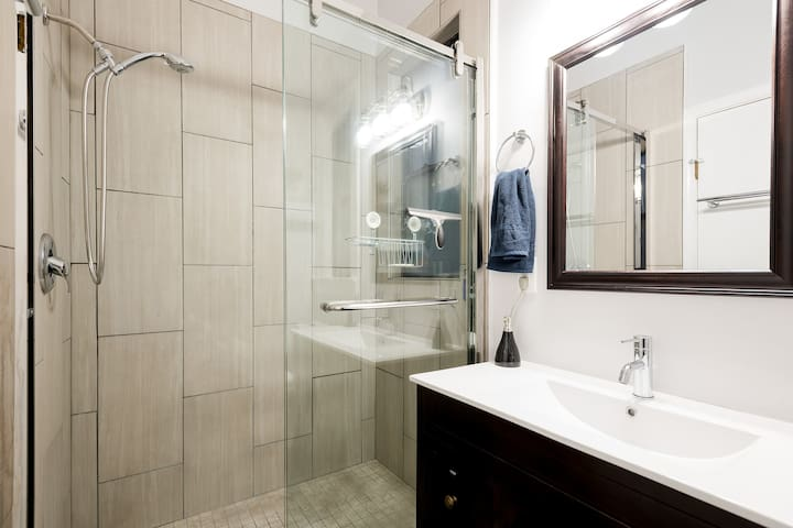 Large glass-paned shower in shared bathroom.