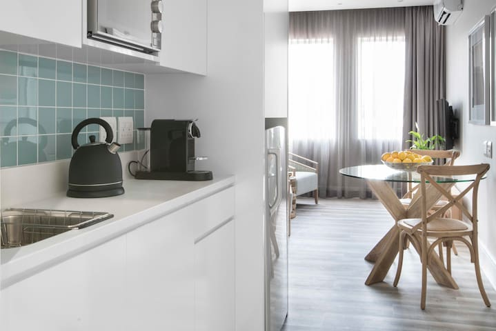 The modern kitchenette includes a Nespresso coffee machine with milk frother, Russell Hobbs kettle, microwave and mini fridge / freezer combo.