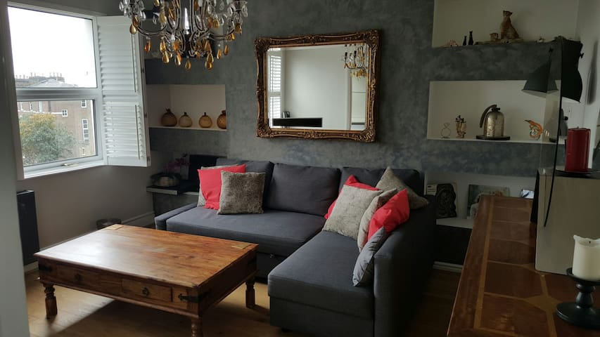 Living room from a different angle.  The room overlooks the high street.  Its furnished to a high standard.