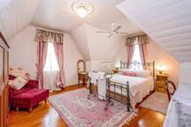 Second attic bedroom with queen size iron bed, wool rugs and pink silk curtains