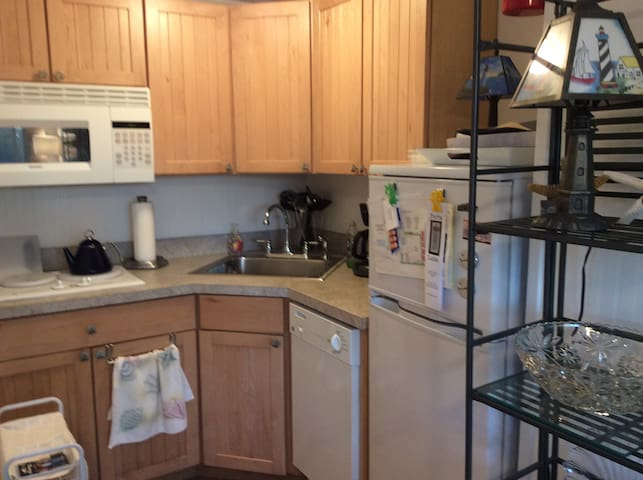 Well-equipped kitchen includes refrigerator, 2 burner stove, microwave, coffee maker, teapot, dishwasher, pots/pans, dishes, glassware, toaster, silverware and utensils...adjacent small table with 4 chairs