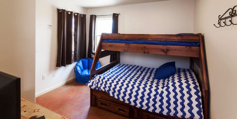 Second bedroom with full (bit smaller than queen) mattress on the bottom, twin on top bunk bed, smart TV.