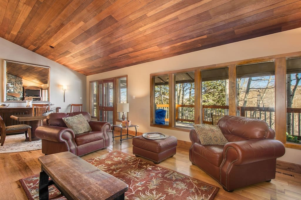 The living room is open, bright and beautifully designed with floor to ceiling windows, hardwood floors throughout and vaulted ceilings.