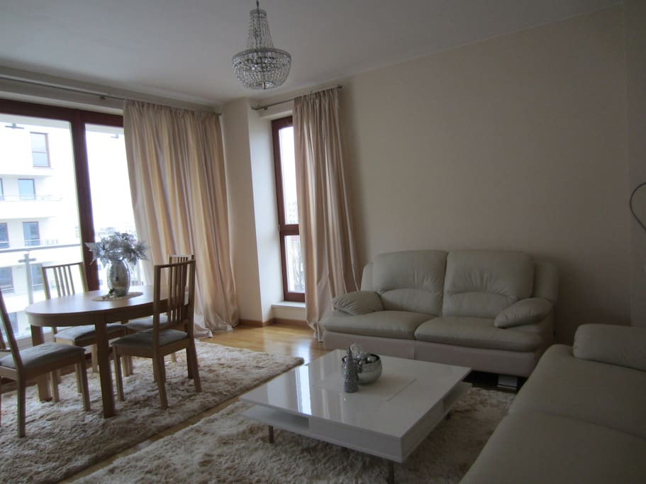 The living room with 3 and 2 seat sofas. Table with 4 chairs. TV, DVD,  HI-FI