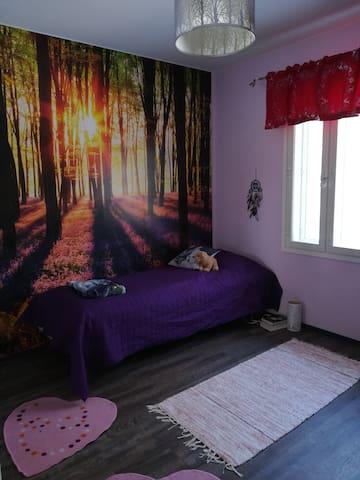 Purple Room, with a bed and 2 air matresses, if needed. A table and chair. / Violetti Huone, jossa on sänky ja jonne sopii hyvin kaksi ilmapatjaa. Pöytä, tuoli ja kokovartalopeili löytyvät myös, sekä lautapelejä.