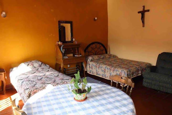 Recámara grande con 1 cama matrimonial y 2 individuales, mesa de trabajo, ropero y secreter