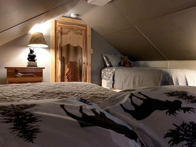 Queen bed and single bed located in the first loft