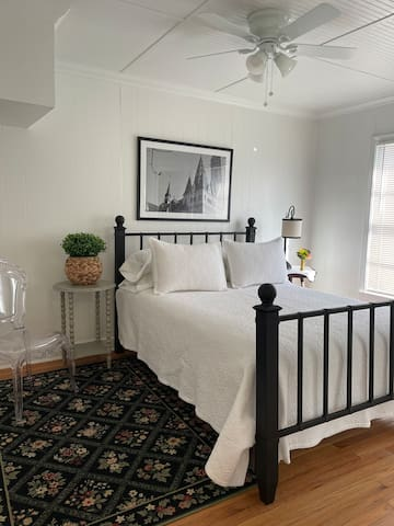 This back bedroom has a black iron bed and queen size mattress. The bed has 800+ thread count sheets and Little Blue Bungalow monogrammed pillows. Hanging in the closet is an LBB monogrammed cotton robe. This room has two closets to hang garments.