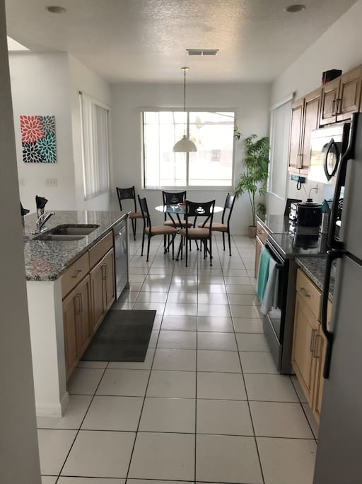 Open kitchen with newly updated appliances, counters, with kitchen table that faces the pool deck and lake.