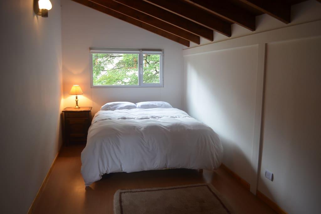Habitación principal con somier, cortinas blackout- roller, cajoneras y estantes para ropa.