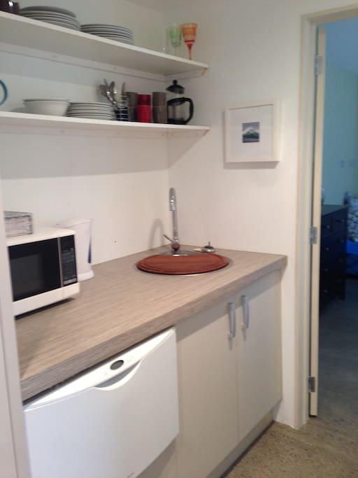 Private use of kitchenette with sink, dishwasher, microwave and plug in cooking appliances.