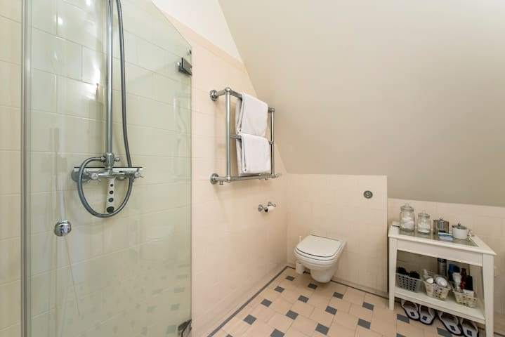 Tiled bathroom with shower and washing machine