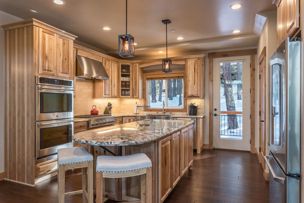 An upgraded kitchen has a granite center island and stainless steel appliances