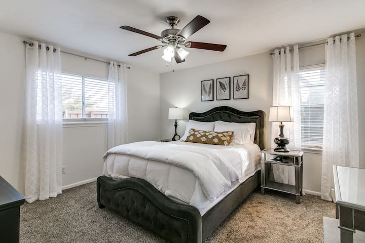 """Master bedroom looks out to deck and patio. Queen bed, spacious closets, and 40"""" TV. The curtains in this room have been changed to black-out curtains."""
