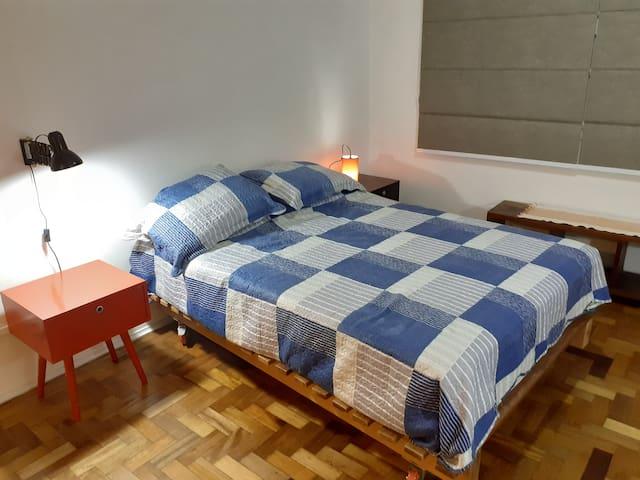 Suite ampla de casal com luminárias para leitura, mesa de cabeceira e janela com persiana black-out.  Quatro travesseiros, colchão e roupa de cama de qualidade para perfeitas noites de sono.