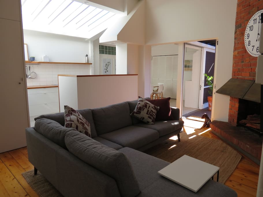LIVING ROOM. Walk down the entrance hall to a spacious, sunny living room with high ceilings a kitchen and dining room.
