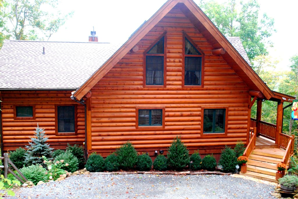 Beautiful, log cabin construction and evergreen landscaping will give