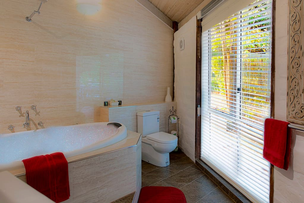 Bathroom with huge two person  Spa in the Sunshine Red Mudbrick Cottage