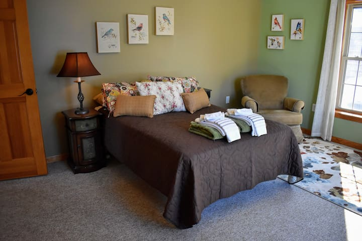 Spacious second bedroom on the main floor with a comfy chair to enjoy a cup of coffee and to watch the wildlife in the backyard.