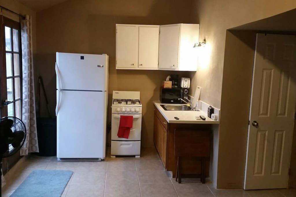 kitchen,microwave, gas stove,refrigerator.
