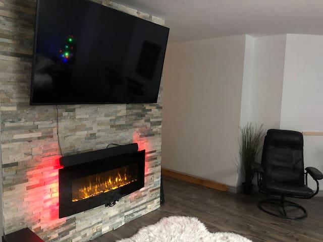 Salon avec divan lit pouvant faire 2 lits simple. Foyer, téléviseur 65 pouces, coin bar avec tabourets. Endroit très relaxant et paisible.