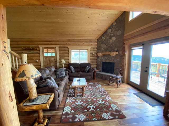Living room with gas fireplace and view of the Rocky Mountains. Queen sofa couch