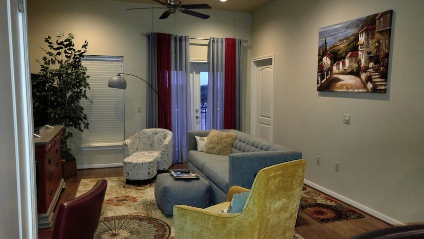 Living area with French doors leading to the balcony overlooking a part of downtown Waco. 49 inch Roku TV for the husband's who want to just hangout and watch sports while the wives are at the Silos or shopping at Spice Village.